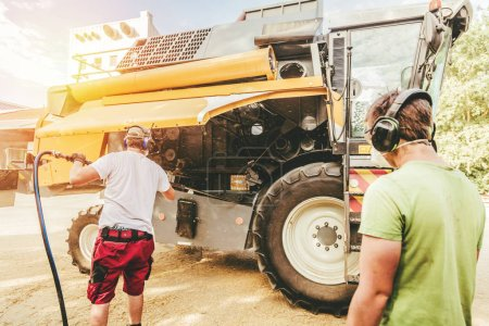 Photo for Mechanics repairing combine harvesters in the farm yard. - Royalty Free Image
