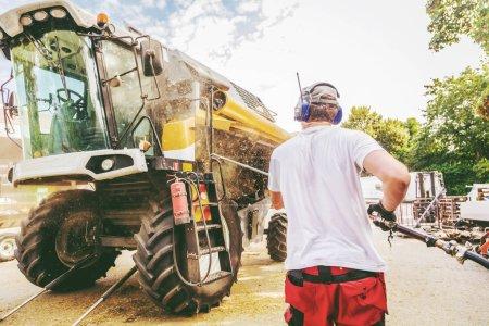 Photo pour Mécanicien réparer la moissonneuse-batteuse jaune et vert dans la cour de la ferme. - image libre de droit