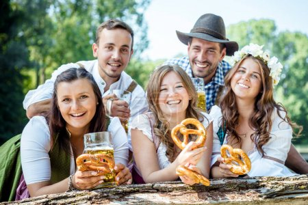 Photo for Five happy young friends in Bavarian costumes holding glasses of beer with pretzels and smiling at camera outdoor - Royalty Free Image