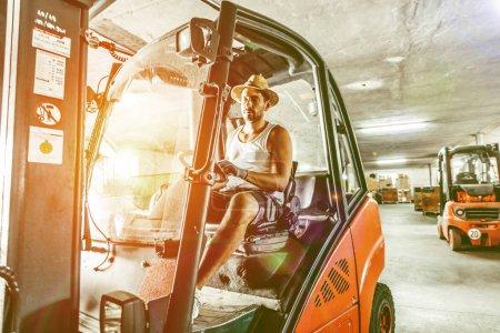 Photo pour Ouvrier d'entrepôt avec chariot élévateur. - image libre de droit