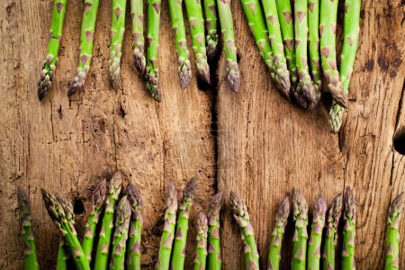 Photo for Top view of fresh ripe green asparagus on wooden background - Royalty Free Image