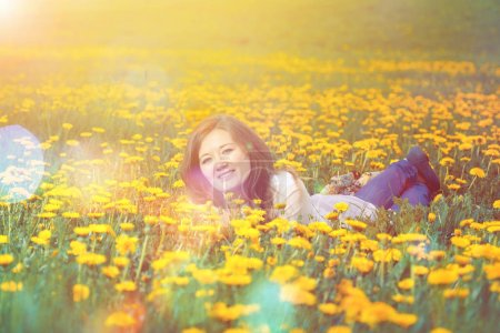 Pretty woman lying down on dandelions field, happy cheerful girl resting on dandelions meadow, relaxation outdoor in springtime, vacation