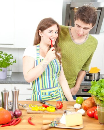 Photo for Happy young man and woman cooking food together in kitchen - Royalty Free Image
