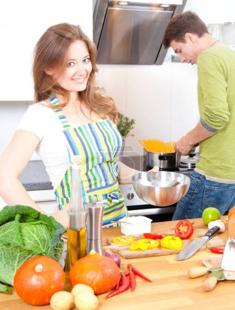 Photo for Young woman in apron smiling at camera while boyfriend cooking spaghetti behind in kitchen - Royalty Free Image