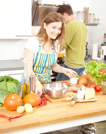 young woman in apron smiling at camera while boyfriend cooking behind in kitchen