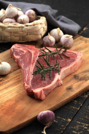 Photo pour Bifteck T-bone cru assaisonné d'épices et d'herbes fraîches servi sur une planche en bois - image libre de droit