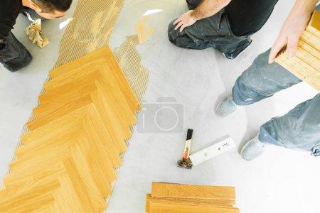 Foto de Tiro recortado de los trabajadores que instalan suelo de parquet de roble durante la mejora del hogar - Imagen libre de derechos