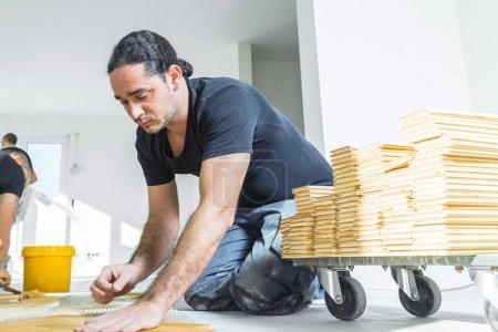 Foto de Trabajadores profesionales instalando suelo de parquet de roble durante la mejora del hogar - Imagen libre de derechos