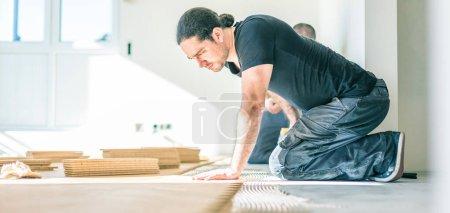 Foto de Trabajadores enfocados instalando suelo de parquet de roble durante la mejora del hogar - Imagen libre de derechos