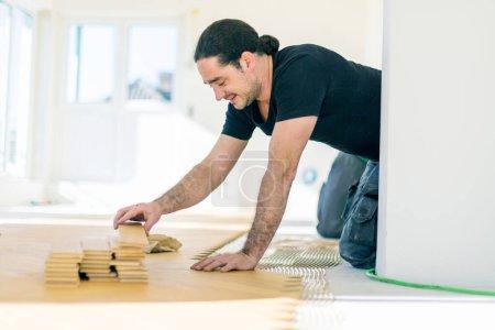 Foto de Hombre sonriente instalación de suelo de parquet de roble durante la mejora del hogar - Imagen libre de derechos