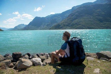 Photo pour Randonneur avec sac à dos se reposer près du lac Gjende au Parc National de Jotunheimen, Norvège - image libre de droit