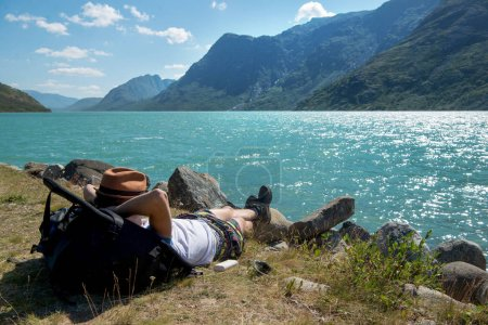 Photo pour Randonneur au repos sur le sac à dos près du lac Gjende au Parc National de Jotunheimen, Norvège - image libre de droit