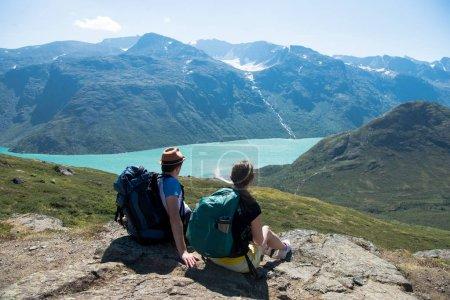 Photo pour Couple de randonneurs se reposant et regardant Besseggen crête sur le lac Gjende dans le parc national de Jotunheimen, Norvège - image libre de droit