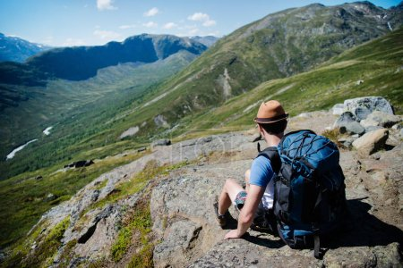 traveler with backpack resting on Besseggen ridge in Jotunheimen National Park, Norway