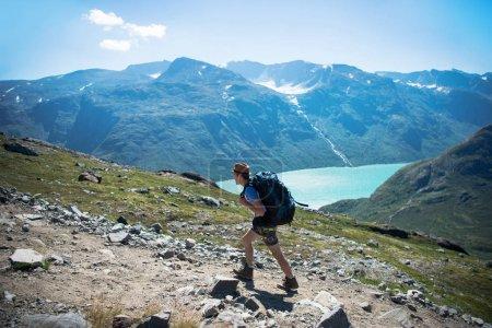Photo pour Randonneur avec sac à dos, marchant sur la crête Besseggen sur lac Gjende au Parc National de Jotunheimen, Norvège - image libre de droit