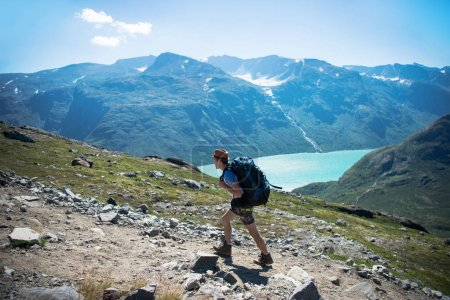 Photo for Hiker with backpack walking on Besseggen ridge over Gjende lake in Jotunheimen National Park, Norway - Royalty Free Image