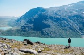 hiker standing on Besseggen ridge and looking at Gjende lake in Jotunheimen National Park, Norway