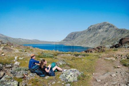two hikers resting on Besseggen ridge over Gjende lake in Jotunheimen National Park, Norway