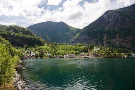 Photo pour Maisons dans le village de Flam près de belles montagnes sur la côte de l'Aurlandsfjord majestueux (Aurlandsfjorden), Norvège - image libre de droit