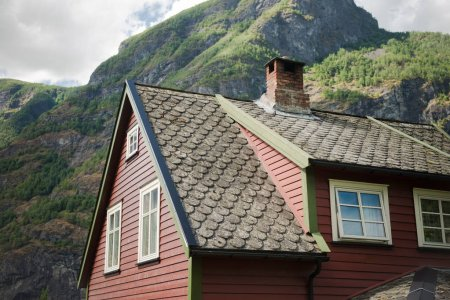 low angle view of beautiful wooden house in Flam village and majestic mountains, Aurlandsfjord (Aurlandsfjorden), Norway