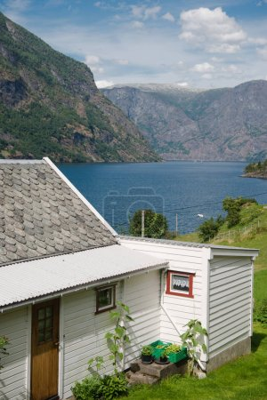 cozy wooden white house and majestic landscape in Gudvangen, Naeroyfjord, Norway