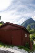 """Постер, картина, фотообои """"коричневый деревянный сарай и красивые горы позади, Аурландс-фьорда, Флам (Aurlandsfjorden), Норвегия"""""""