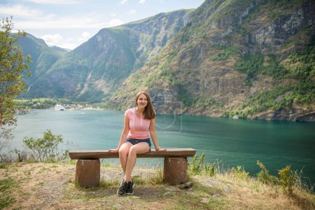 Photo pour Belle jeune femme regardant caméra alors qu'elle était assise sur un banc en bois près d'Aurlandsfjord et de montagnes majestueuses, Flam (Aurlandsfjorden), Norvège - image libre de droit