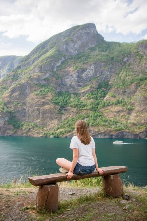 Photo pour Vue arrière de la jeune femme assise sur un banc en bois et regardant un paysage majestueux, Aurlandsfjord, Flam (Aurlandsfjorden), Norvège - image libre de droit