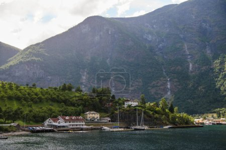 buildings and yachts moored on calm lake near beautiful mountains in Norway