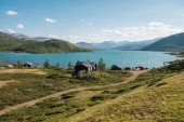 """Постер, картина, фотообои """"деревянные здания в уютной деревне у озера Йенде, гряда Бессегген, Национальный парк Йотунхеймен, Норвегия"""""""