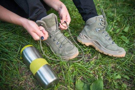 Photo pour Recadrée tir du touriste femme attacher lacets sur l'herbe verte - image libre de droit