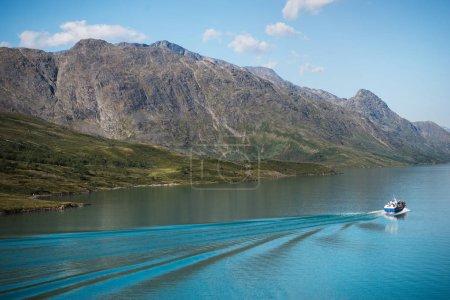 Photo pour Bateau flottant sur les eaux calme du majestueux lac Gjende, crête Besseggen, Parc National de Jotunheimen, Norvège - image libre de droit