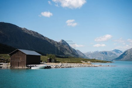 wooden barn and boat on coast of majestic Gjende lake, Besseggen ridge, Jotunheimen National Park, Norway