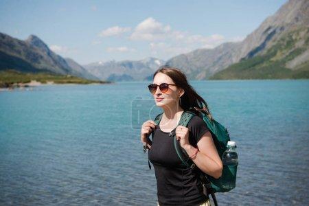 Foto de Hermosa mujer joven en gafas de sol con pie mochila cerca de majestuoso lago Gjende, canto de Besseggen, Parque Nacional de Jotunheimen, Noruega - Imagen libre de derechos