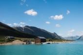 """Постер, картина, фотообои """"здания на берегу величественного озера Йенде, хребта Бессегген, Национальный парк Йотунхеймен, Норвегия"""""""