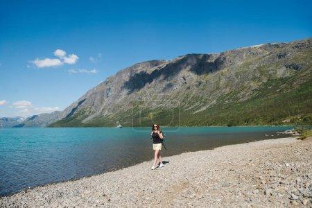 Foto de Hermosa mujer joven con mochila caminar cerca del lago Gjende, canto de Besseggen, Parque Nacional de Jotunheimen, Noruega - Imagen libre de derechos