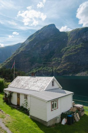 AURLANDSFJORD, FLAM, NORWAY - 27 JULY, 2018: high angle view of cozy white house and majestic mountains at Aurlandsfjord, Flam (Aurlandsfjorden), Norway