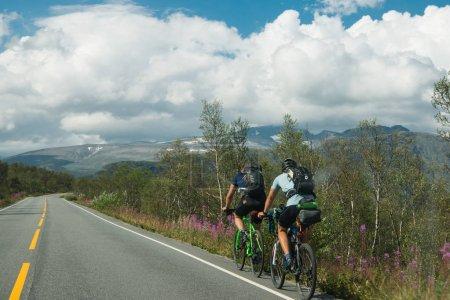 Photo pour Norvège - 26 juillet 2018: vue de deux hommes bicyclettes à cheval sur la route menant à la montagne dans le Parc National de Hallingskarvet arrière - image libre de droit