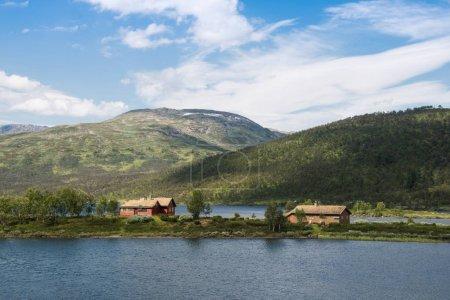 Photo pour Bâtiments sur la petite île avec des montagnes derrière, Parc National de Hallingskarvet, Norvège - image libre de droit