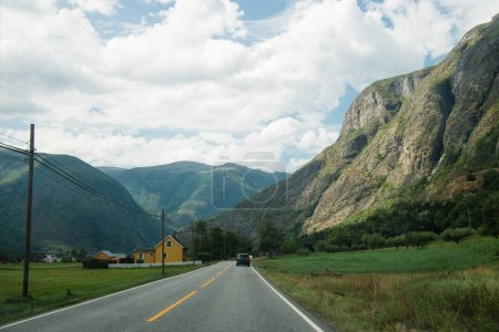 Photo for Distant view of car moving on road to mountains, Hallingskarvet National park, Norway - Royalty Free Image