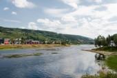 """Постер, картина, фотообои """"удаленный вид здания на берегу реки с зеленого холма, крупнейшего горнолыжного курорта в Трюсиле, Норвегия"""""""