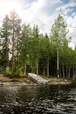 Photo pour Bateau en bois près du lac en face de la forêt à Trysil, la plus grande station de ski de Norvège - image libre de droit