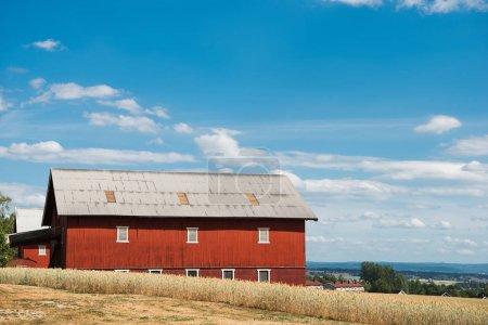 red farm building under blue cloudy sky, Hamar, Hedmark, Norway