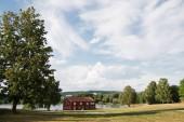 """Постер, картина, фотообои """"Красный дом возле озера под пасмурным небом, Хамар, Хедмарк, Норвегия"""""""