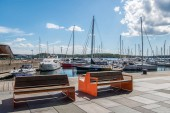 OSLO, NORWAY - 28 JULY, 2018: empty wooden benches on embankment and moored boats in harbour at Aker Brygge district, Oslo
