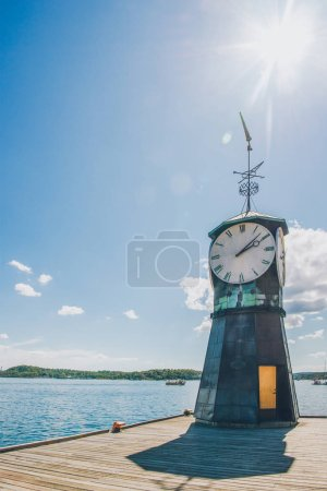 Photo for Low angle view of clock on wooden pier at oslo harbour, norway - Royalty Free Image