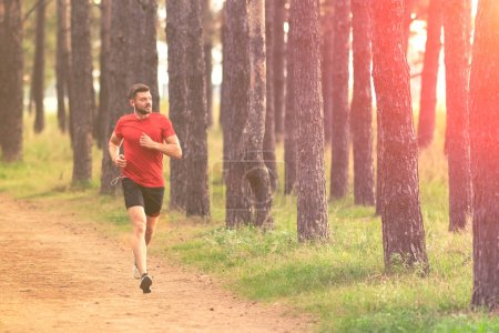 Photo for Running man. Male runner jogging at the park. Guy training outdoors. Exercising on forest path. Healthy, fitness, wellness lifestyle. Sport, cardio, workout concept - Royalty Free Image