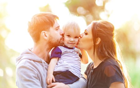 Photo for Young parents hugging and kissing her baby. Happy family outdoors. - Royalty Free Image