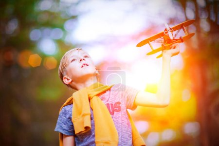 Photo pour Beau garçon jouant avec l'avion jouet jaune à l'extérieur. Rêves de voyage - image libre de droit