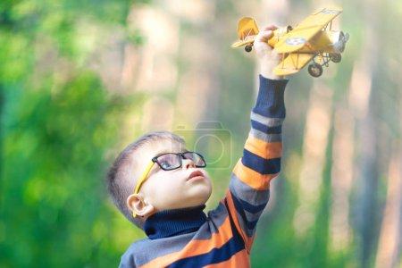 Photo pour Petit garçon drôle portant des lunettes jouant avec un avion jouet à l'extérieur. Rêves de voyage - image libre de droit
